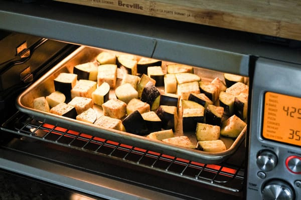 Sheet pan with eggplant cooking in toaster oven.