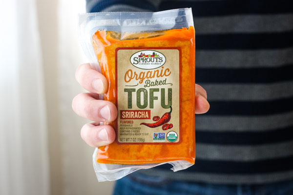 A hand holding a package of sriracha baked tofu.
