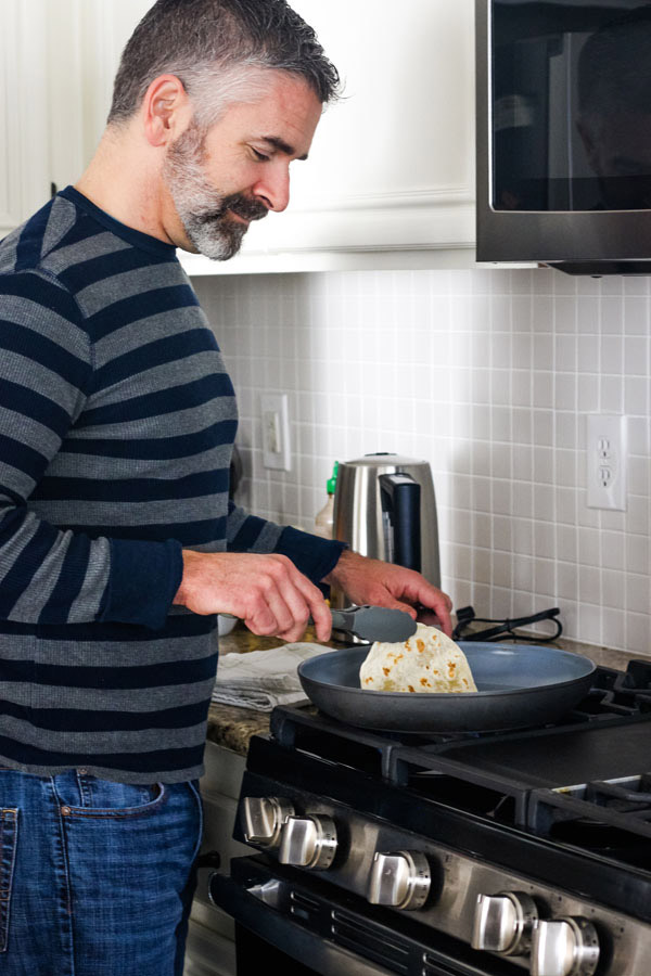 Man warming tortillas in a skillet on a stovetop.