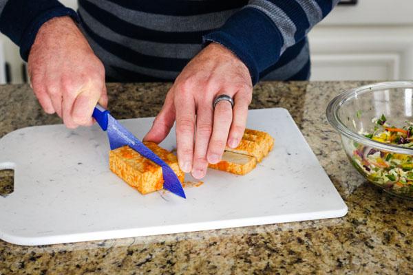 Hands slicing sriracha baked tofu on a cutting board.