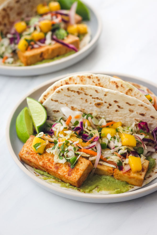 Tofu Tacos with Mango Slaw on a blue plate with lime wedges.