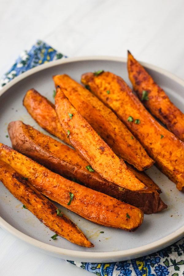 Smoky sweet potato wedges on a blue plate.