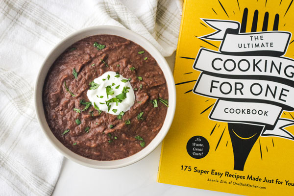 Black bean soup in a white bowl next to a cooking for one cookbook.