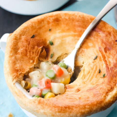 Fork scooping filling out of an individual pot pie.