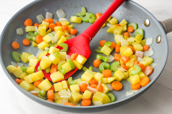 Vegetables cooking in a skillet.