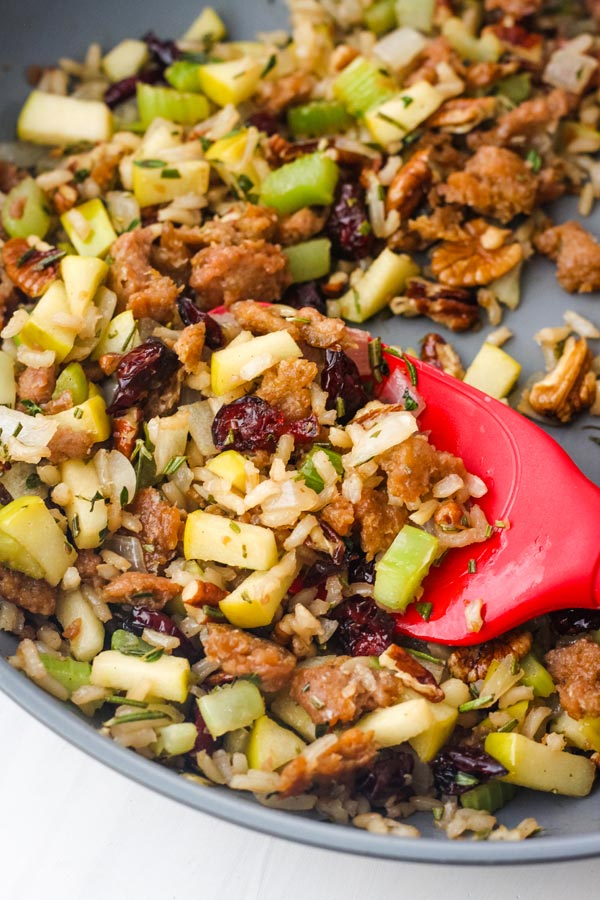 Vegetarian sausage and apple stuffing cooked in a skillet.