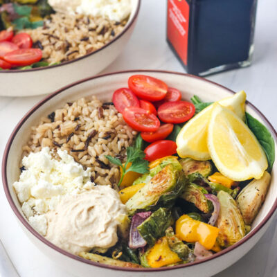 Two tan bowls with grains and roasted vegetables with a bottle of balsamic vinegar.