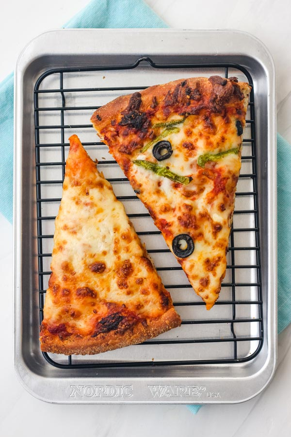 Overhead view of warmed cheese and veggie pizza slices on a mini rack inside a small pan.