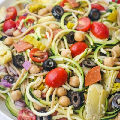 Closeup of a tossed zucchini pasta salad in a large white bowl.