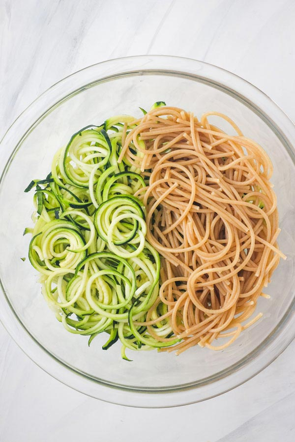 Zucchini noodles and cooked spaghetti noodles in a glass bowl.