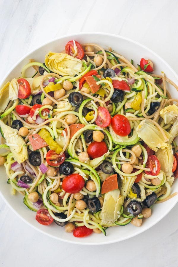 Overhead view of a big bowl of zucchini pasta salad on a white table.