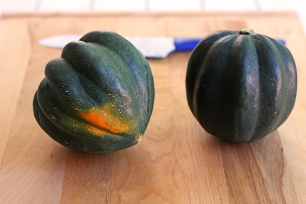 two acorn squashes on a cutting board with knife
