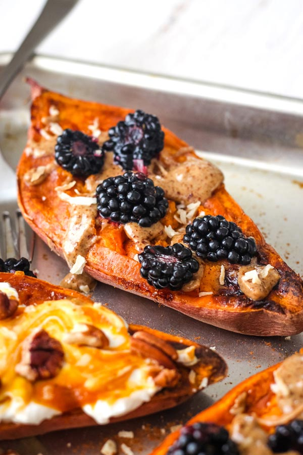 Sweet potato halves on a quarter sheet pan with peanut butter and berries.