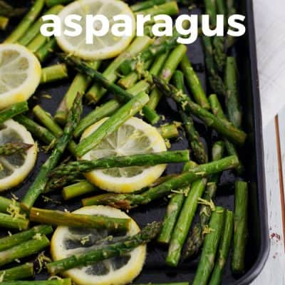 Chopped and roasted asparagus spears with lemon wedges on a black toaster oven pan