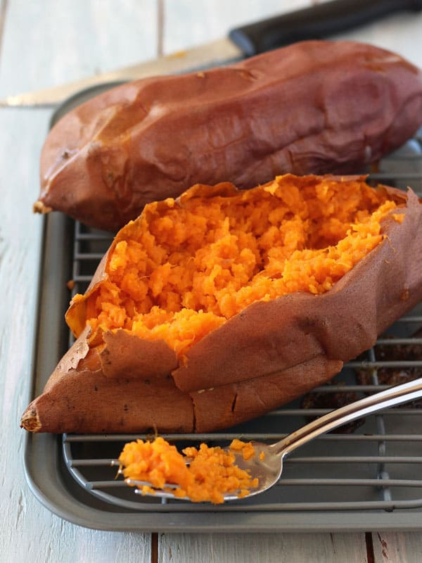 Baked sweet potato sliced open and fluffed with a fork.