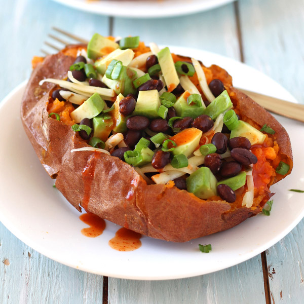 A blue table with a white plate with a fork and stuffed sweet potato.
