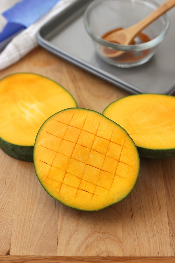 A cutting board with mango sliced in half and scored in a crosswise pattern.