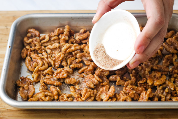 A hand shaking cinnamon sugar over toasted walnuts on a sheet pan.