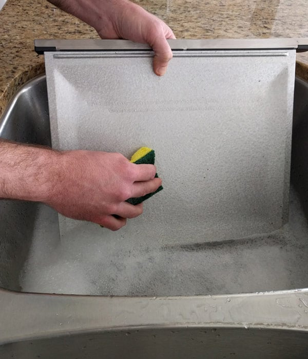 Man washing a crumb tray in soapy water with a yellow sponge.