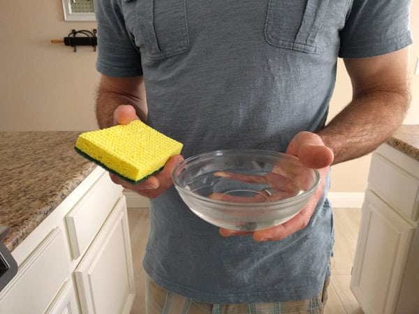Man holding a yellow sponge and bowl of warm water.