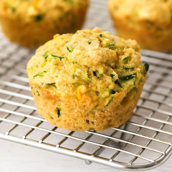 zucchini muffins cooling on a silver metal baking rack.