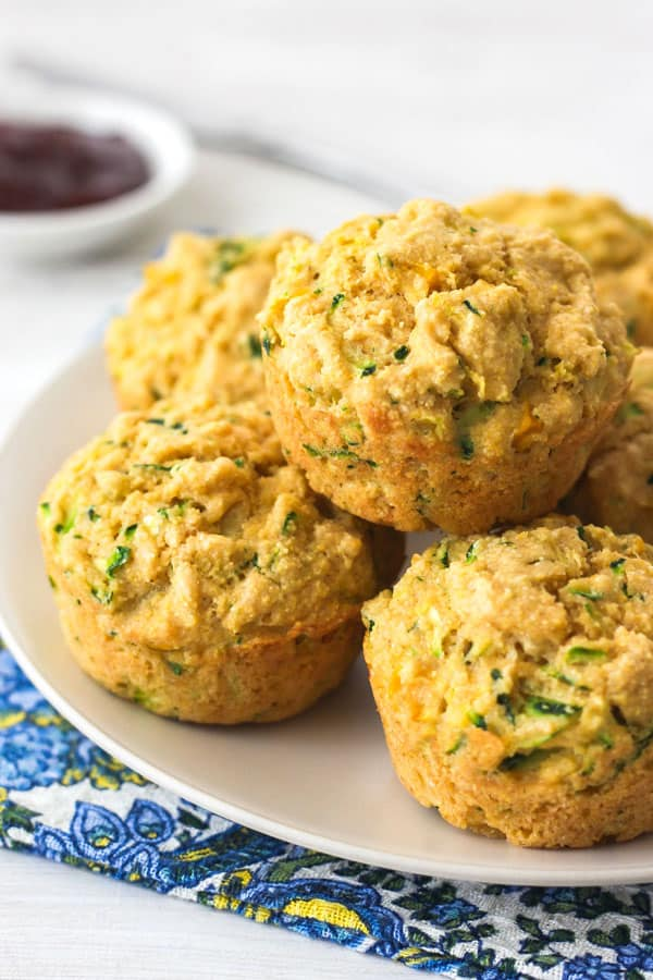 Cornbread zucchini muffins stacked on a tan plate on top of a blue paisley napkin.