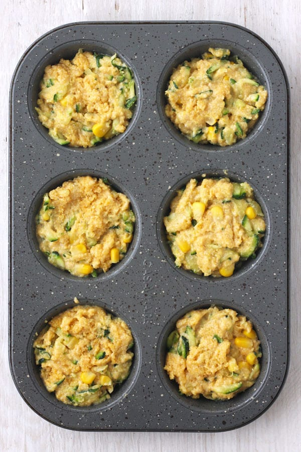 Cornbread zucchini batter in a gray metal muffin tin on a white wood background.
