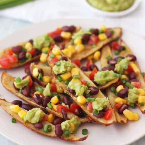 Potato skin strips on a plate with bean salsa and guacamole.