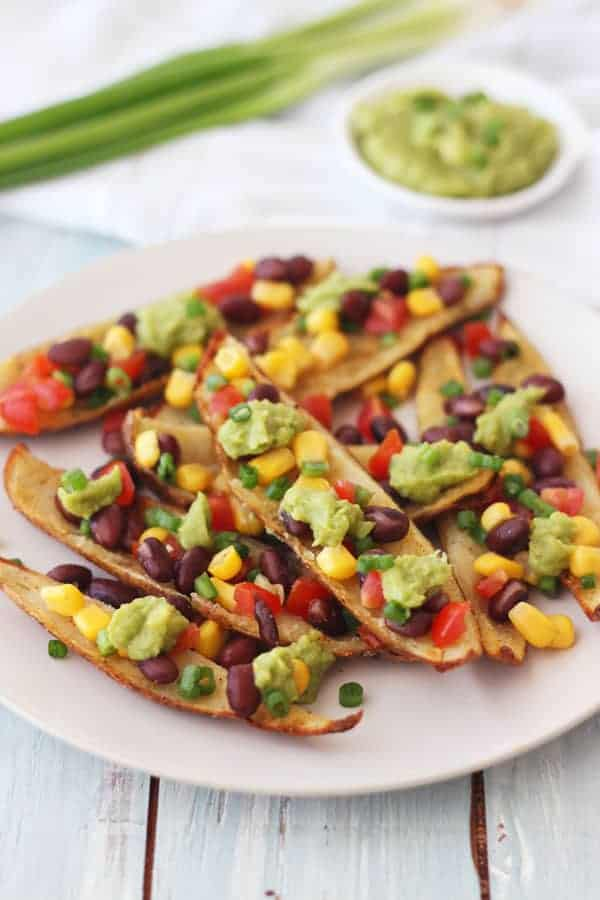 Potato skin strips on a plate with beans, salsa, and guacamole.