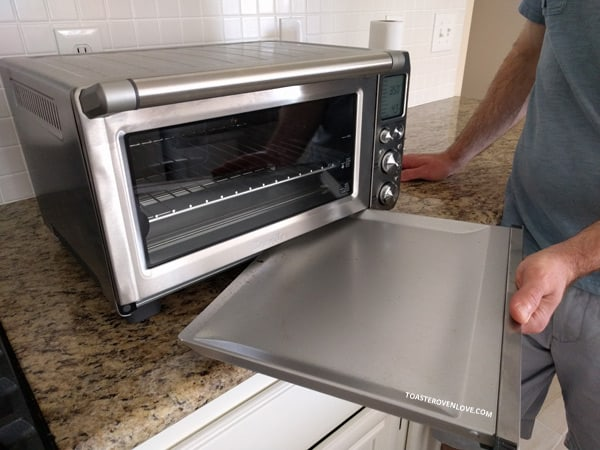 Man removing a crumb tray from a toaster oven.