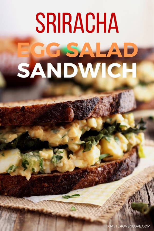 A creamy sriracha egg salad on two slices of toasted bread with flaky kale chips in the middle.