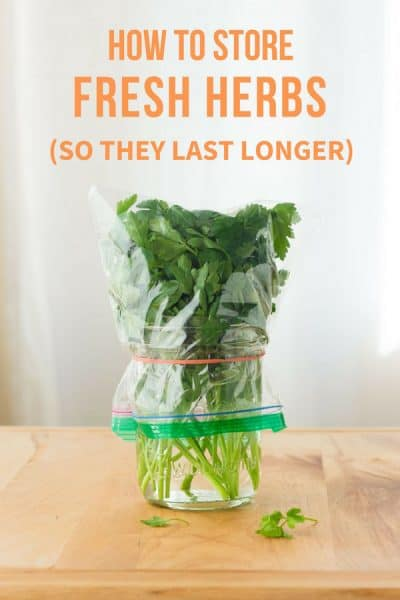 Fresh herbs in a jar covered with a plastic bag.