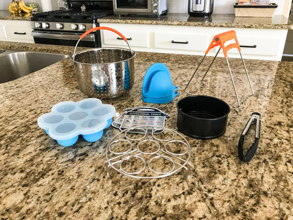 Instant Pot Mini Accessories (steam basket, small springform pan, plate grabber, egg rack) on a kitchen counter.