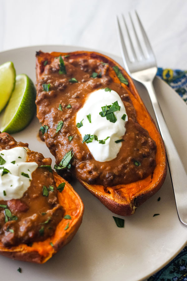 A plate with a fork and sweet potato halves topped with lentils and yogurt.