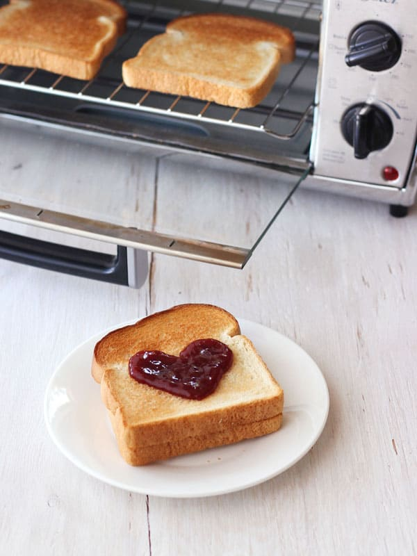 Toast with a jelly heart on a white plate.