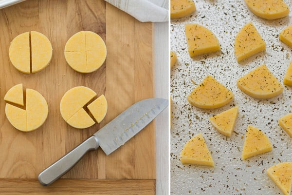 Polenta circles sliced into triangles on a cutting board and baking sheet.