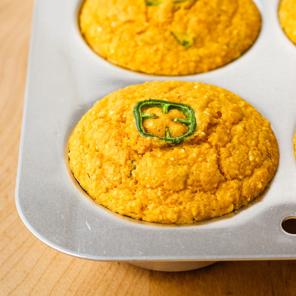 Cornbread muffins in a muffin pan on a cutting board.