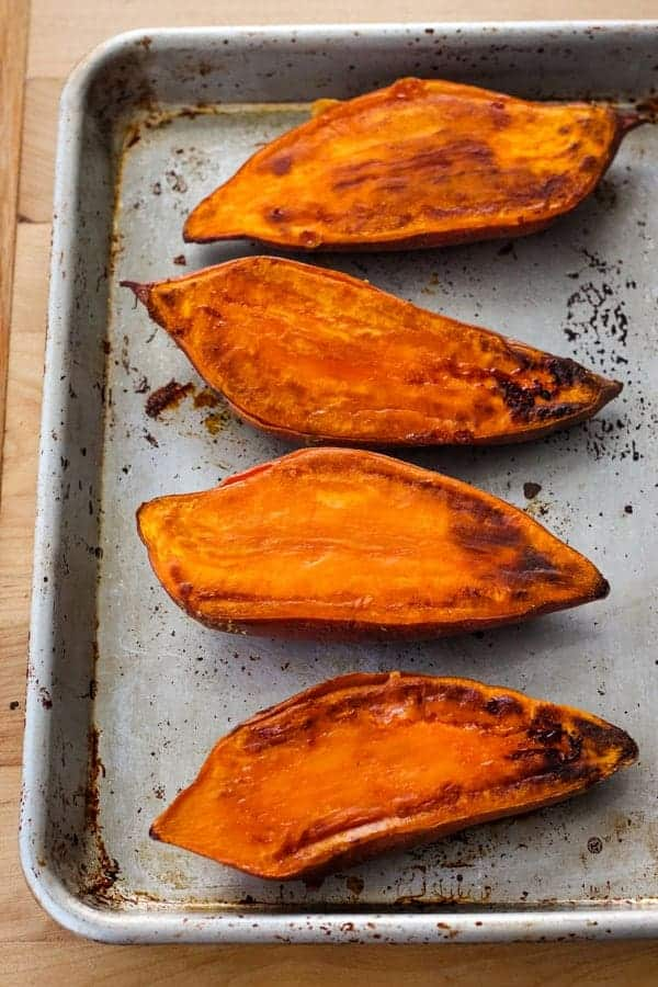 Cooked sweet potato halves on a quarter sheet pan.