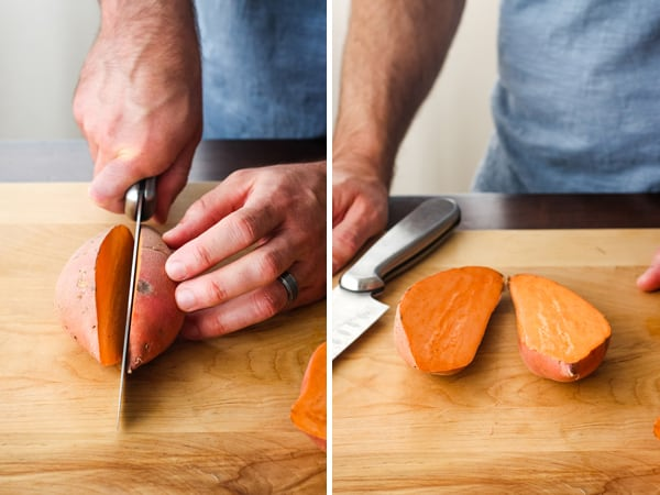 Hand slicing a sweet potato in half on a cutting board.
