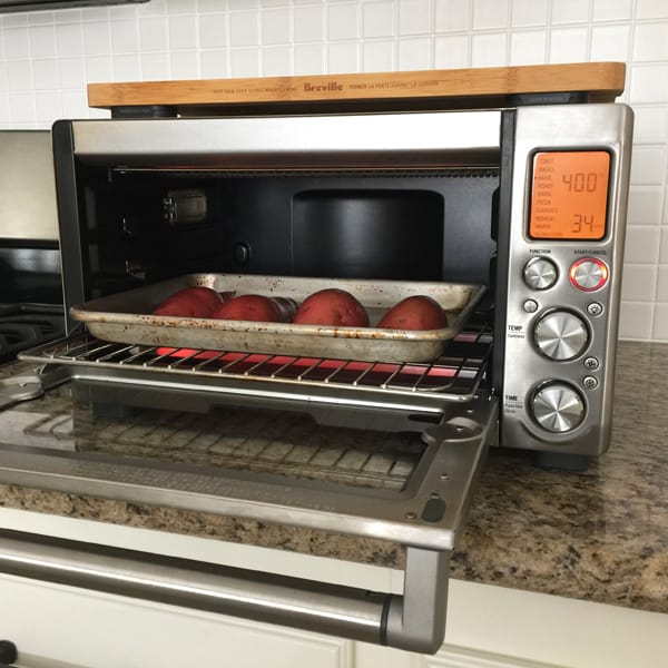 A quarter sheet pan of sweet potatoes inside a Breville Smart Oven Pro.