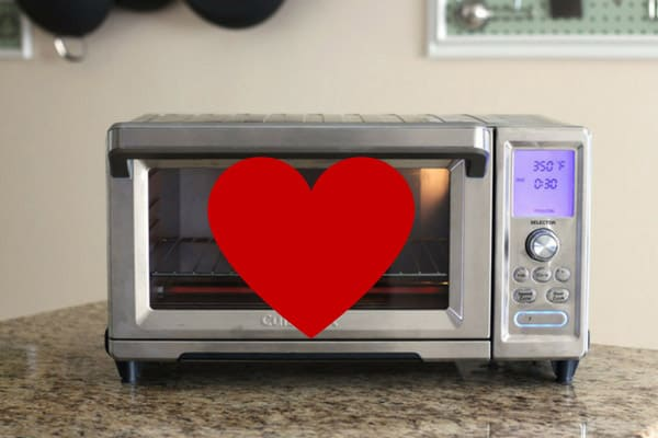Toaster oven on a kitchen counter with a red heart over it.