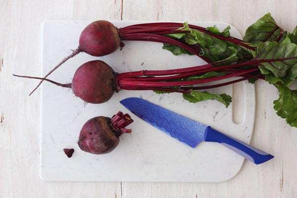 Red beets with leaves attached on a cutting board.
