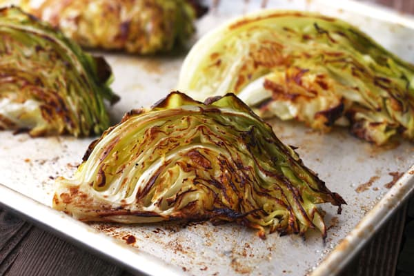 Golden roasted cabbage on a baking sheet.