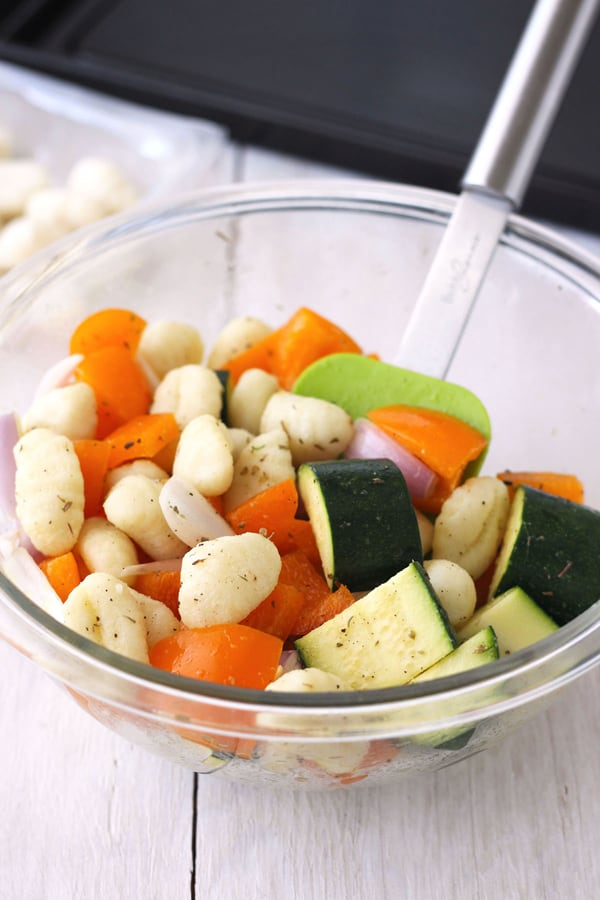 Gnocchi with chopped zucchini, orange bell pepper and shallots in a bowl