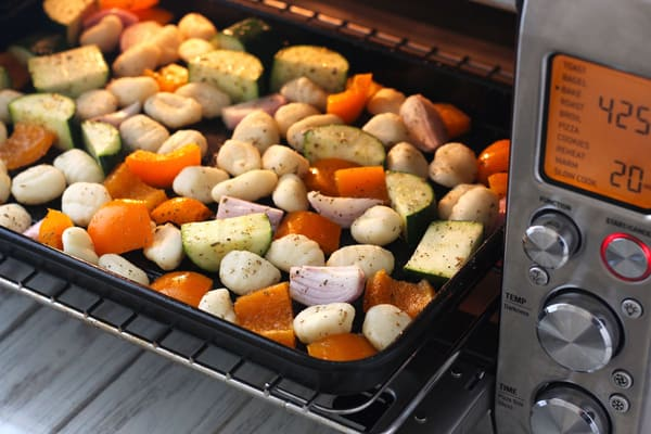 Gnocchi and Vegetables roasting on a pan in a toaster oven