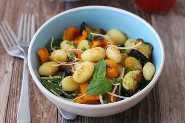 A blue bowl with roasted gnocchi and vegetables on a wooden table.