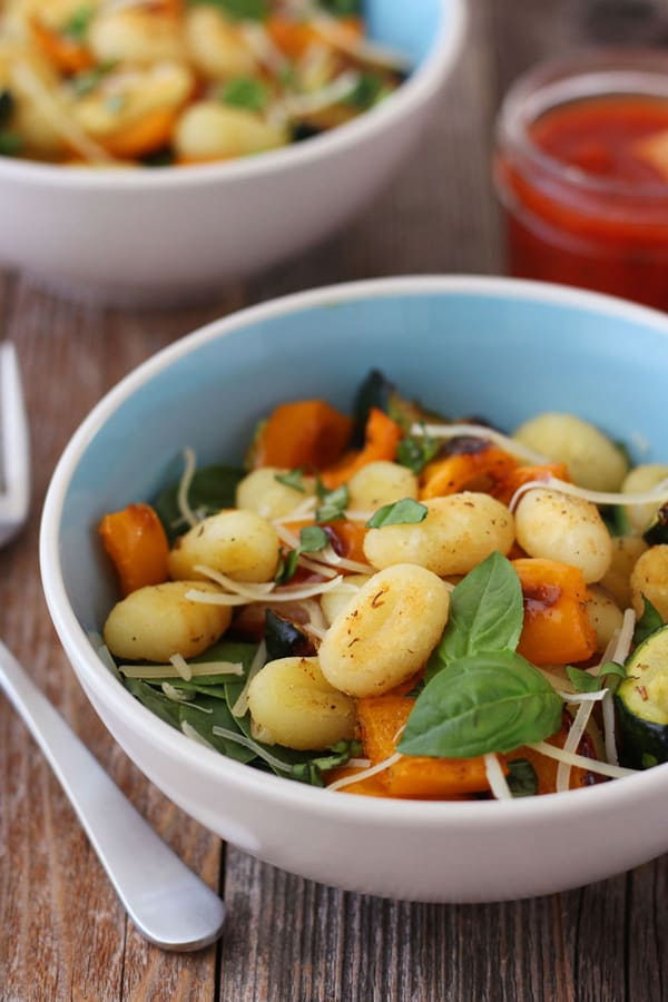 A blue bowl with gnocchi and spinach