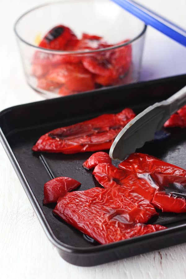 Roasted red peppers with blackened spots on a roasting pan.