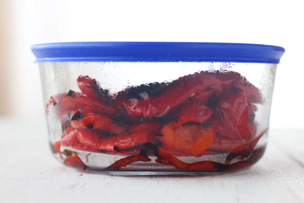 Roasted red peppers steaming in a covered container.