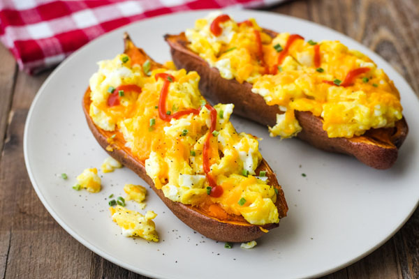 A tan plate with scrambled egg topped sweet potatoes.